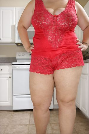 Full figured Caucasian young woman in sexy red lingerie standing in kitchen. Stock Photo - 2168207