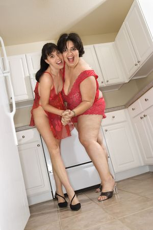 frolic: Caucasian young women in sexy red lingerie smiling and dancing in kitchen. Stock Photo