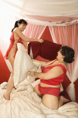 Young Caucasian women in sexy red lingerie having pillow fight in bed. photo