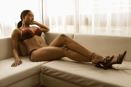 Young African American woman reclining on couch in lingerie and heels. Stock Photo - 2167848
