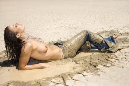 wet breast: Topless Caucasian mid-adult woman covered in mud lying in desert with head back.