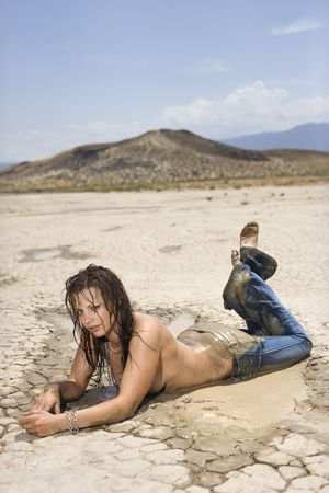 topless jeans: Topless Caucasian mid-adult woman covered in mud lying on stomach in desert looking at viewer.  Stock Photo