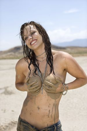 Topless Caucasian mid-adult woman holding breasts covered in mud in desert smiling and looking at viewer. Stock Photo - 2167955