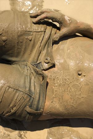 iszapos: Midriff shot of Caucasian mid-adult woman covered in mud taking off her jeans.