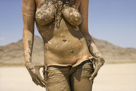 hot breast: Torso shot of topless Caucasian mid-adult woman covered in mud taking off her jeans in desert.