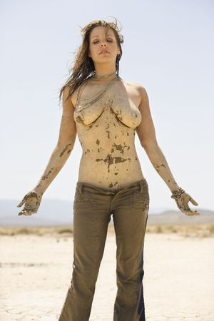 Topless Caucasian mid-adult woman covered in dried mud standing in desert. photo