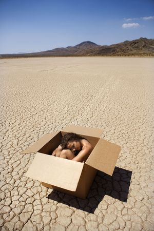 Pretty nude young woman sitting in box in cracked desert landscape in California.