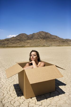 Pretty  young woman sitting in box in cracked desert landscape in California.