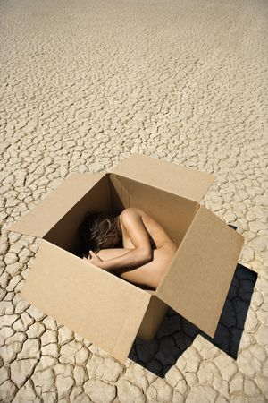 Pretty nude young woman curled up in fetal position inside box in cracked desert landscape in California. photo