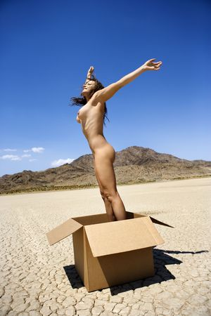 Pretty nude young woman jumping energetically out of box in cracked desert landscape in California. photo