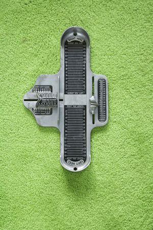 Vintage foot size measuring device against green carpet.
