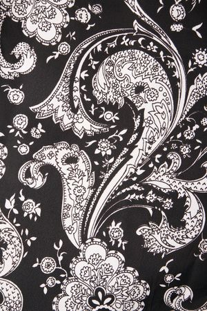 Close-up of black and white vintage fabric with flowers and paisley printed on polyester.