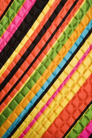 quilted: Close-up of bright colorful striped quilted vintage fabric.