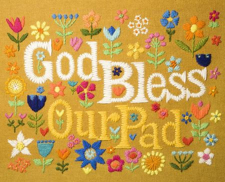 god bless: Vintage needlepoint wall hanging of colorful flowers surrounding the phrase God Bless Our Pad.