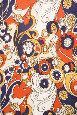Close-up of vintage fabric with red blue and gold flowers and swirls printed on polyester.