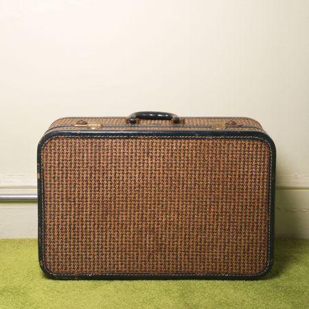 green carpet: Still life of brown retro suitcase on green carpet. Stock Photo