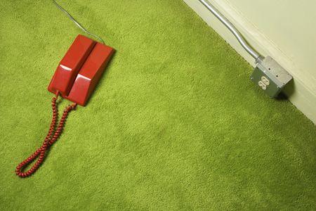 green carpet: Red vintage telephone on 70s green carpet.