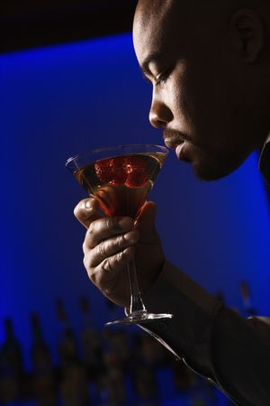vertical bars: Profile of African American man drinking martini in bar against glowing blue background.