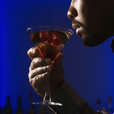 profile: Close up profile of African American man drinking martini in bar against glowing blue background.