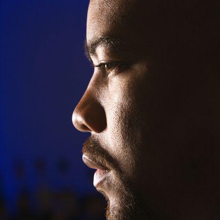 Primo piano di profilo African American uomo nella barra contro incandescente sfondo blu.
