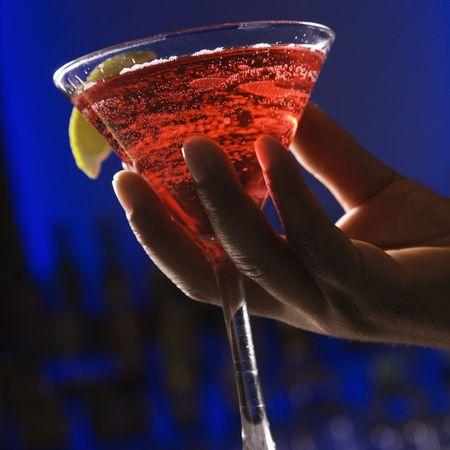 bebidas alcoh�licas: Mano masculina americana africana que sostiene martini en barra contra fondo azul que brilla intensamente.