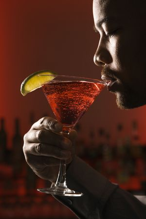 vertical bars: African American man drinking martini in bar against glowing red background.