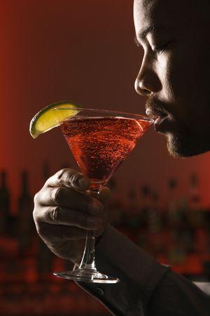 intoxicant: African American uomo che beve martini in bar contro sfondo rosso incandescente.
