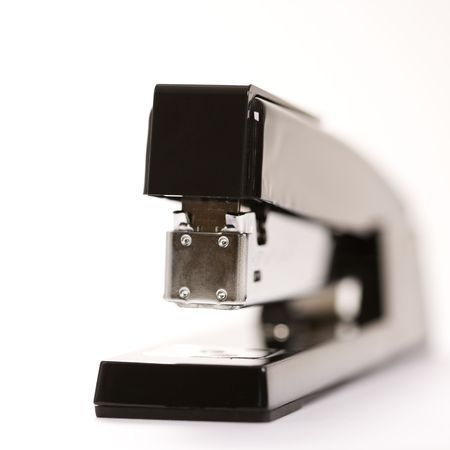 Selective focus of black stapler on white background. photo