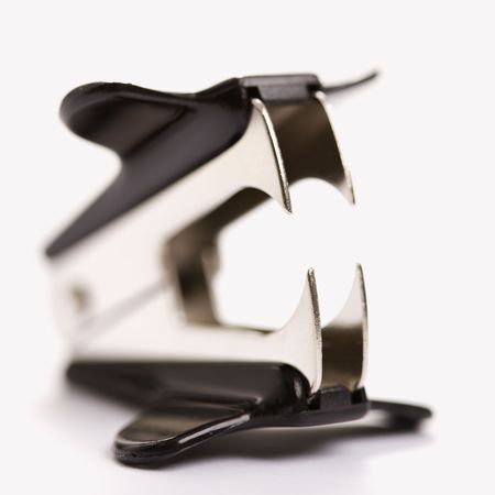 menacing: Staple remover on white background with selective focus.