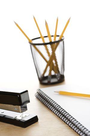 Pencils, a stapler, and spiral bound notebooks arranged on a desk. photo