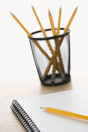 Pencils and spiral bound notebooks arranged on a desk. photo