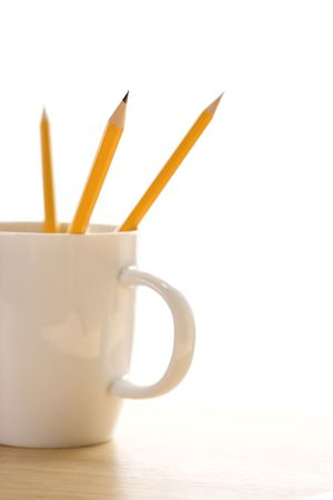 ends: Three pencils in a coffee cup with pointed ends up. Stock Photo