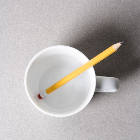 high angle: High angle view of a pencil in an empty white coffee cup.