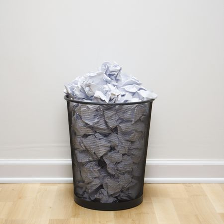 wastebasket: Wire mesh trash can filled with crumpled paper.