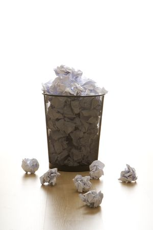wire mesh: Full wire mesh trash can with crumpled paper scattered around.