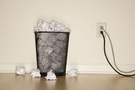 wire mesh: Full wire mesh trash can with crumpled paper next to electrical outlet and plugs. Stock Photo