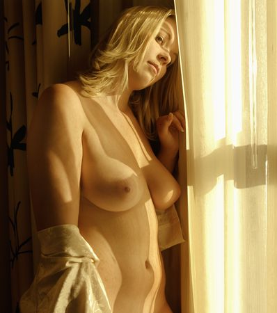 Caucasian young adult nude woman standing by window.