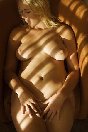 half nude: Caucasian young adult nude woman lying down with eyes closed. Stock Photo