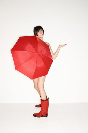 wellies: Young sexy Caucasian woman in red boots holding red umbrella and checking for raindrops. Stock Photo