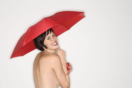 half length posed: Shirtless young Caucasian woman smiling at viewer and holding red umbrella.