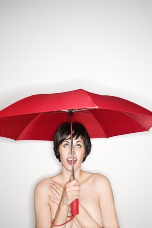 brolly: Shirtless young Caucasian woman holding red umbrella and looking up.
