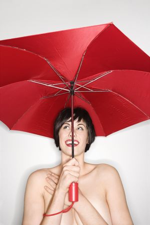 Shirtless young Caucasian woman holding red umbrella and smiling. photo