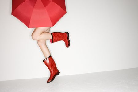 wellies: Legs of young Caucasian woman in red boots holding red umbrella and jumping.