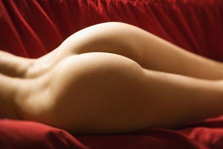 buttock: Derriere de sexy desnudos de mujeres adultas j�venes de raza cauc�sica seduce por mentir sobre el sof� rojo.  Foto de archivo