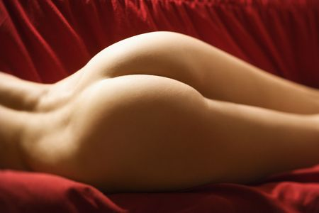 woman buttocks: Derriere of sexy nude Caucasian young adult female lying seductively on red couch.