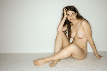 Nude Caucasian young woman sitting on floor with hand to head looking at viewer.