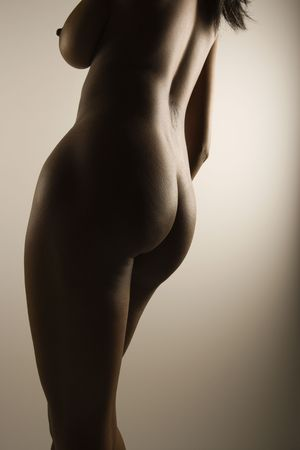 sensuality: Nude African American mid adult female with back to viewer showing breast and hips.