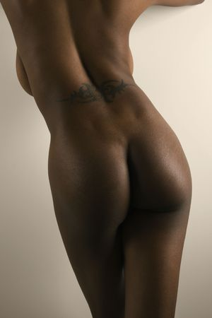 nude butt: Nude African American mid adult female standing with back tattoo. Stock Photo