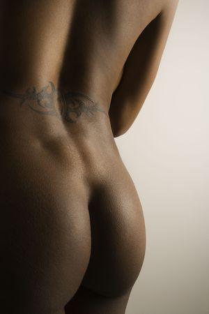 Nude African American mid adult female buttocks and  back with tattoo.