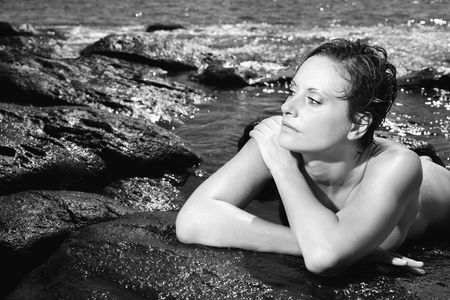 half nude: Mid adult nude Caucasian woman lying on stomach in water at Maui, Hawaii beach. Stock Photo